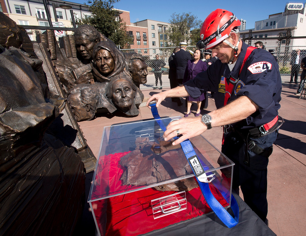 """. John Farrell, an urban search and rescue specialist for the Oakland Fire Department, attaches a strap to a lucite box containing a piece of steel from the twin towers of the World Trade Center, at a ceremony to dedicate the final section of \""""Remember Them,\"""" artist Mario Chiodo\'s paean to heroes of civil rights and humanity, Thursday, Feb. 21, 2013 in Oakland Calif. Farrell was a member of the search and rescue team from northern California that helped with recovery efforts following the 9/11 attacks. (D. Ross Cameron/Staff)"""
