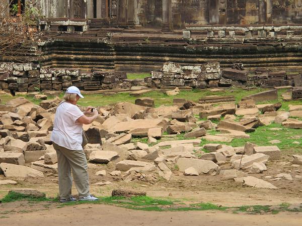 Gretchen Lengyel taking a photograph of Bayon.