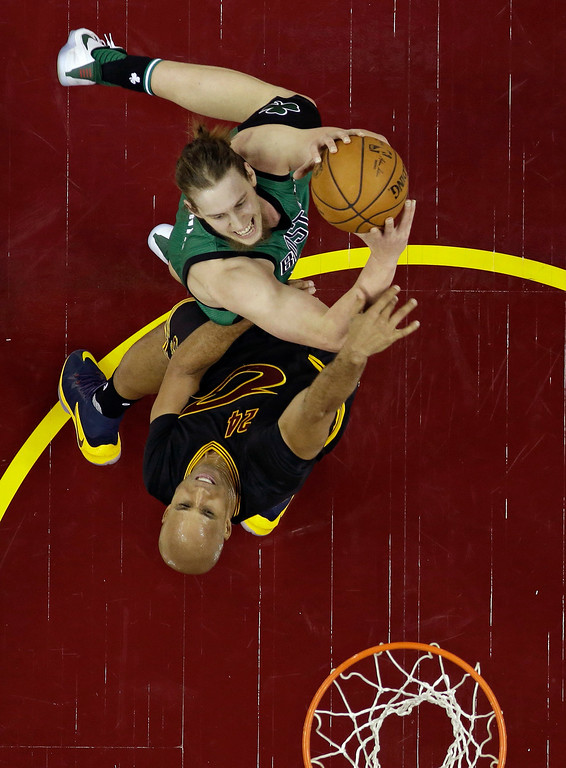 . Boston Celtics\' Kelly Olynyk, top, drives to the basket against Cleveland Cavaliers\' Richard Jefferson in the first half of an NBA basketball game, Thursday, Dec. 29, 2016, in Cleveland. (AP Photo/Tony Dejak)