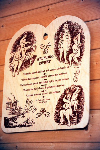 "2011/11/26 – OK, this is a little scandalous, but I've spent the past two days rebuilding our sauna after pulling it apart to repair a water leak. Once done we fired it up to 160 degrees and spent two hours in it. This wood panel has illustrations and instructions in Finnish on the steps to take when you take a sauna. It is on the inside of the sauna and as I was laying there I thought, ""there's my picture for today."" I had a hard time shooting the image before the lens would fog up, but I eventually got it."