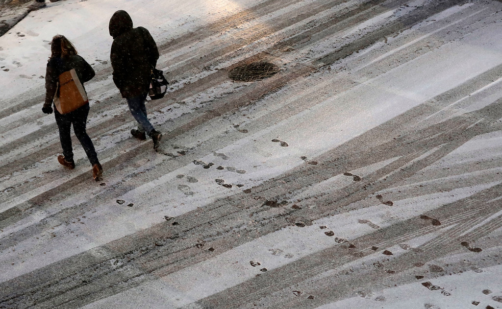 . Pedestrians leave footprints in the snow as they cross a street in downtown Kansas City, Mo., on Saturday, Dec. 17, 2016. A winter storm of snow, freezing rain and bone-chilling temperatures hit the nation\'s mid-section and East Coast on Saturday. (AP Photo/Charlie Riedel)