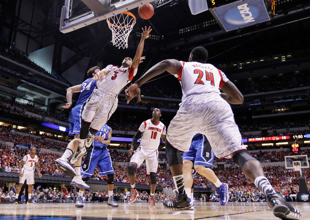 . Louisville guard Peyton Siva (3) goes up for a shot against Duke forward Ryan Kelly (34) during the first half of the Midwest Regional final in the NCAA college basketball tournament, Sunday, March 31, 2013, in Indianapolis. (AP Photo/Michael Conroy)