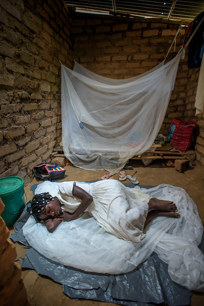 """Kapinga Alphoncine, 13 yr-old girl, sleeps on top of an old mosquito net and plastic sheet in the same room with her widowed grandmother.  She lives with her grandmother, Kapinga Godelive, 66 and her 3 brothers: 1-Francois Ngondo, 14 2-Mbuyamba Phillip, 9 3-Beya Honore, 6 Kananga, DRC Democratic Republic of Congo.  Inside Kapinga's four-room house the walls are paint splattered. There is little furniture except for two small tables and an old cabinet. On top sits a dusty old television. A peek behind reveals that it has no cord. Kapinga sits on a low, wooden bench against one wall reading an old school exercise book of English lessons. """"Good morning my friends, good morning.""""  Her English is good in spite of a mispronunciation here and there. High up on the wall to the right is a crucifix. It's as battle worn as the rest of the house. Light streams in through the numerous holes in the tin-sheeted roof. In the yard outside, the house is ringed on all sides with gardens of potato and cassava leaves, sorrel and sugarcane among other things.  In one corner of the yard a few visitors gather on homemade chairs under a thatched-roof patio. Across the compound the afternoon sun throws light on the smaller of the two buildings there. In chalk, just below the roof line are the words, """"Il n'ya pas de rose sans epines."""" There is no rose without thorns.  Home Life Her family is living with her grandmother since her dad died. Her mom went off to look for work. She has 3 brothers,1 older and 2 younger. 1-Francois Ngondo, 14 2-Mbuyamba Phillip, 9 3-Beya Honore, 6  She helps her grandmother by sweeping the compound, washing dishes, working in the garden and doing a little cooking. Kapinga sleeps on tattered sheets of plastic. She also puts down a mosquito net but sleeps on top of it.  School Kapinga doesn't attend school right now. She used to but had to stop when her father died because they don't have the money for school fees. She was in grade 7 which is the first grade of high s"""