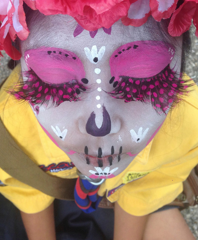 ". Girl scout Luna Hernandez, 9, dressed as a ""Catrina,\"" or skeleton lady, waits for the start of the Gran Procession of the Catrinas, to mark the upcoming Day of the Dead holiday, in Mexico City, Sunday, Oct. 23 2016. The gran procession is one of many that will take place in Mexico City as part of the celebrations, culminating with visits to the graves of departed loved ones on Nov. 1 and 2. The figure of a skeleton wearing broad-brimmed hat was first done as a satirical engraving by artist Jose Guadalupe Posada sometime between 1910 and his death in 1913, to poke fun at women who pretended to be European by dressing elegantly and as a critique of social stratification. (AP Photo/Anita Baca)"