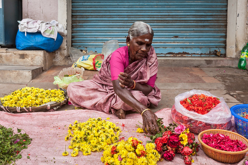 TIRUCHIRAPALLI, INDIA - FEBRUARY 14, 2013: Unidentified Indian woman - hawker (street vendor) of flowers for temple offerings