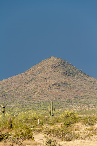 A desert mountain lit by the morning sun with dark, ominous clouds