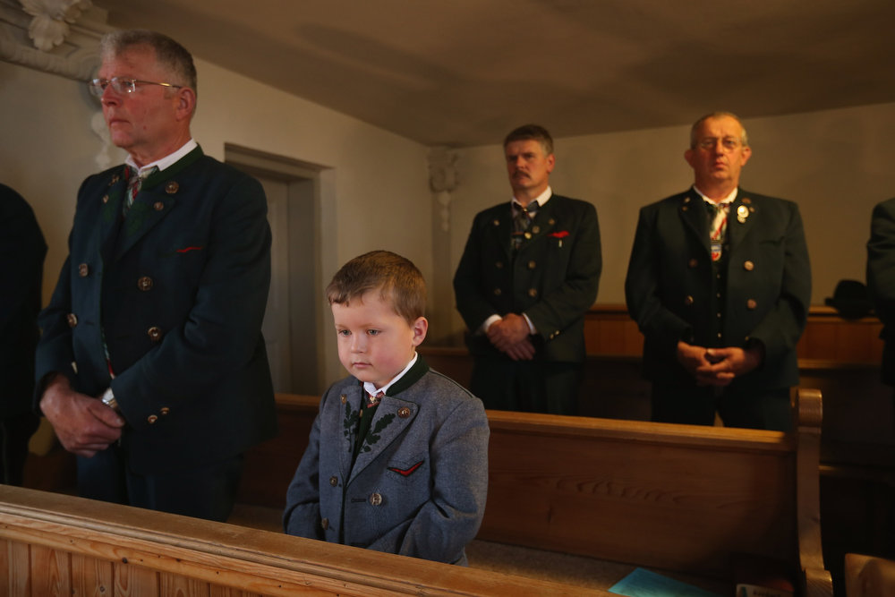 . A boy and men dressed in traditional Bavarian folk costumes attend the annual Corpus Christi (in German called Fronleichnam) mass at St. Michael\'s Church on May 30, 2013 in Seehausen am Staffelsee, Germany. The Seehausen Corpus Christi celebration usually includes a procession to a chapel across the nearby Staffelsee lake, though rain forced organizers to cancel the lake procession this year. Corpus Christi is among the highlights of the Catholic religious calendar in Bavaria.  (Photo by Sean Gallup/Getty Images)