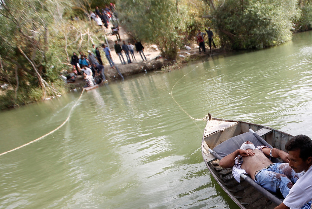 . A wounded Syrian man lies on a boat as he is transferred to Turkey over the Orontes river on the Turkish-Syrian border near the village of Hacipasa in Hatay province October 10, 2012. Scores of Syrian civilians, many of them women with screaming children clinging to their necks, crossed Orontes, a narrow river marking the border with Turkey as they fled the fighting in Azmarin and surrounding villages. Residents from the Turkish village of Hacipasa, nestled among olive groves, helped pull them across in small metal boats. REUTERS/Osman Orsal