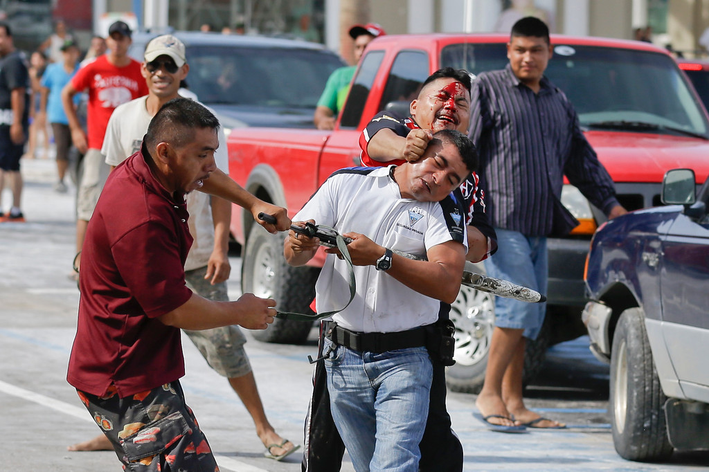 . A man holding an air rifle in a white jersey fights with two other men as he tries to stop looters from storming into the Mega Supermarket in Los Cabos, Mexico, Tuesday, Sept. 16, 2014. According to employees the supermarket donated all the food in the store and established a system by which every person had 5 minutes to get whatever they could for free. Fights broke as other people inciting the crowd to loot. Desperate locals and tourists were in survival mode in the resort area of Los Cabos also on Wednesday, with electrical and water service still out three days after Hurricane Odile made landfall as a monster Category 3 storm. (AP Photo/Victor R. Caivano)