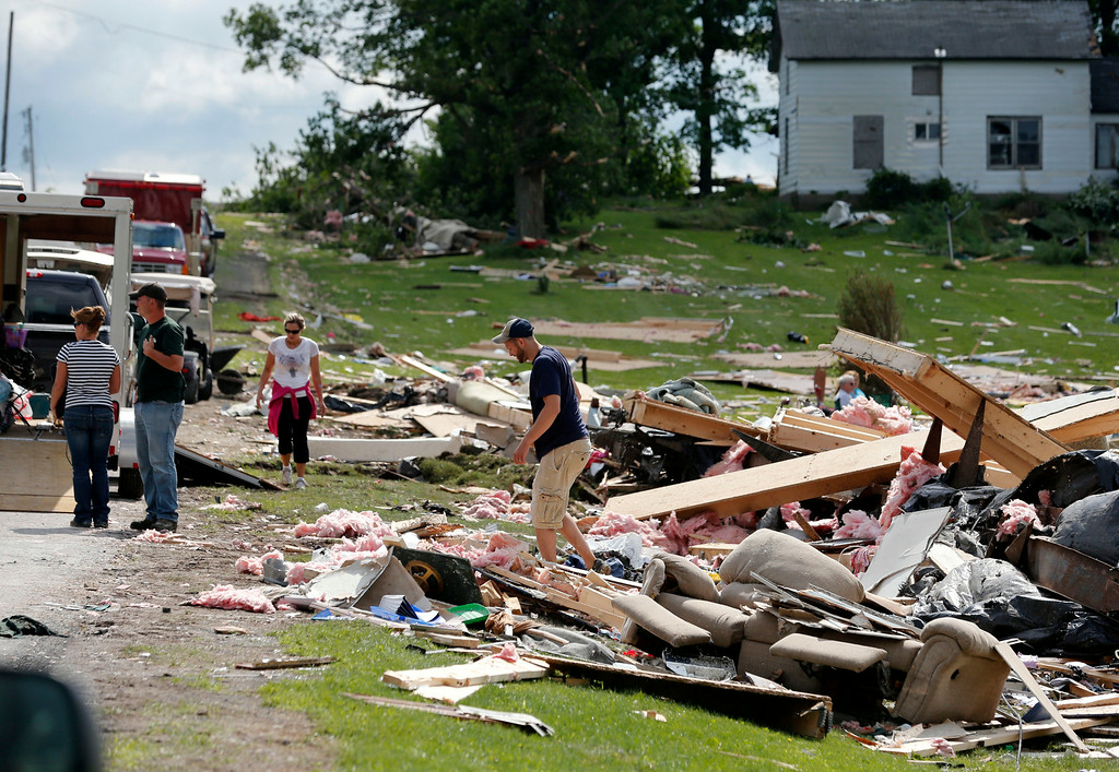 . People sort through debris of a destroyed house after Tuesday night\'s storm, on Wednesday, July 9, 2014, in Smithfield, N.Y.  (AP Photo/Mike Groll)