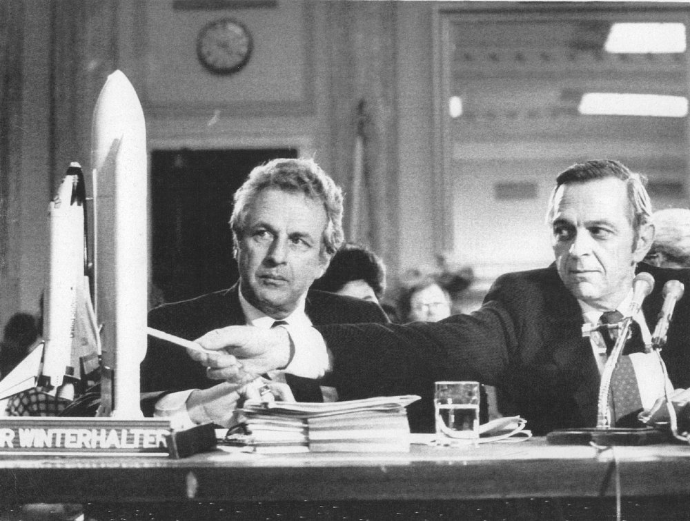 Description of . Jesse Moore, associate NASA administrator (R), points to a model of a space shuttle as David Winterhalter, director of NASA's propulsion division, looks on during the first day of a Congressional hearing into the shuttle Challenger's January explosion on Feb. 18, 1986.   Credit: UPI