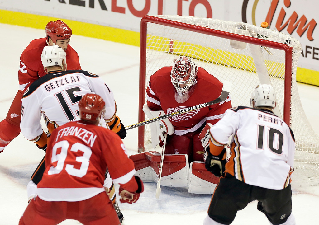 . Anaheim Ducks\' Ryan Getzlaf (15) puts a shot into the top corner of the goal against Detroit Red Wings goalie Jimmy Howard (35) to defeat the Red Wings 3-2 as Detroit Red Wings\' Johan Franzen (93) and Jonathan Ericsson (52), both of Sweden, look on with Anaheim Ducks\' Corey Perry (10) during the third period of an NHL hockey games Saturday, Oct. 11, 2014, in Detroit. (AP Photo/Duane Burleson)