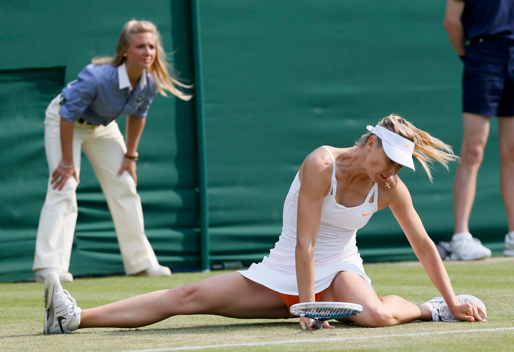 . Maria Sharapova of Russia slips during her women\'s singles tennis match against Michelle Larcher De Brito of Portugal at the Wimbledon Tennis Championships, in London June 26, 2013.       REUTERS/Stefan Wermuth