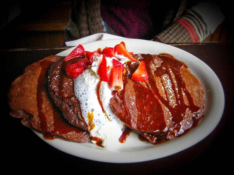 Happy breakfast, chockolate pancakes with strawberries