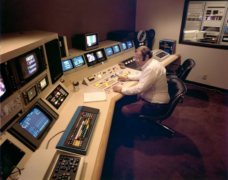 "JTB in Edit Control Room at ARDEV Palo Alto circa 1981. That's the front end of a million bucks of video gear, a CMX edit controller, Grass Valley 1600 switch, ADDA still stores (100 frames!), character generator, not seen: 3 1"" Sony type C VTRs, Quantel freeze frame and1/4 frame repositioning video effect box. ARDEV stood for Atlantic Richfield Development Systems. We were working on a film based floppy videodisc and funded by the huge oil profits of the era. The target customer was the US Military for training systems. We hadn't dreamed of the internet then. Exxon and Atlantic Richfield both got into and out of optical memories at about the same time. ARDEV was sold to McDonnell Douglas which became a part of Boeing. Atlantic Richfield was sold to British Petroleum and is currently leaking oil in the Gulf of Mexico."