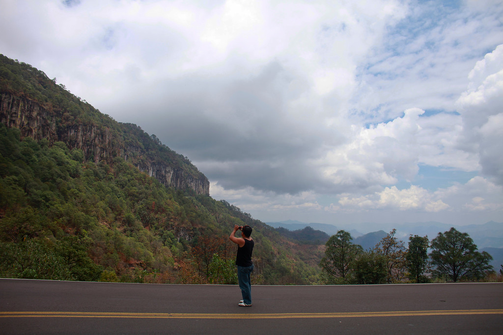 . In this June 12, 2013 photo, a man takes a photo of the landscape as he stands on the old Durango-Mazatlan highway, also known as the Espinazo del Diablo, or Devli\'s Backbone near the town of El Palmito, Mexico.  Sinaloa state tourism officials predict an ìexplosionî for the resort city of Mazatlan, hard hit by drug violence in recent years, as the new road gives Mexicans in interior states an easy drive to the beach. (AP Photo/Dario Lopez-Mills)