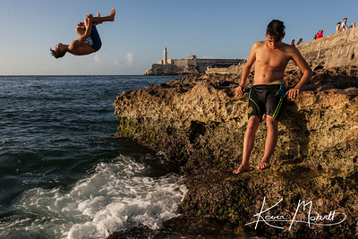 HAVANA - Boys dive off of El Malecón on Havana's coast to escape the summer heat.