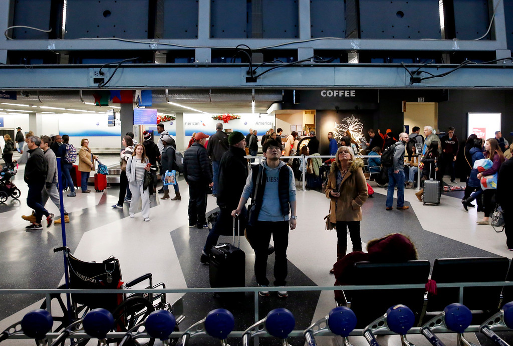 . Travelers check their flight information in Terminal 3 at O\'Hare International Airport in Chicago, Wednesday, Nov. 23, 2016. While driving remains the most popular form of transportation Thanksgiving travelers take, AAA expects just under 4 million people to fly to their holiday destinations. (AP Photo/Nam Y. Huh)