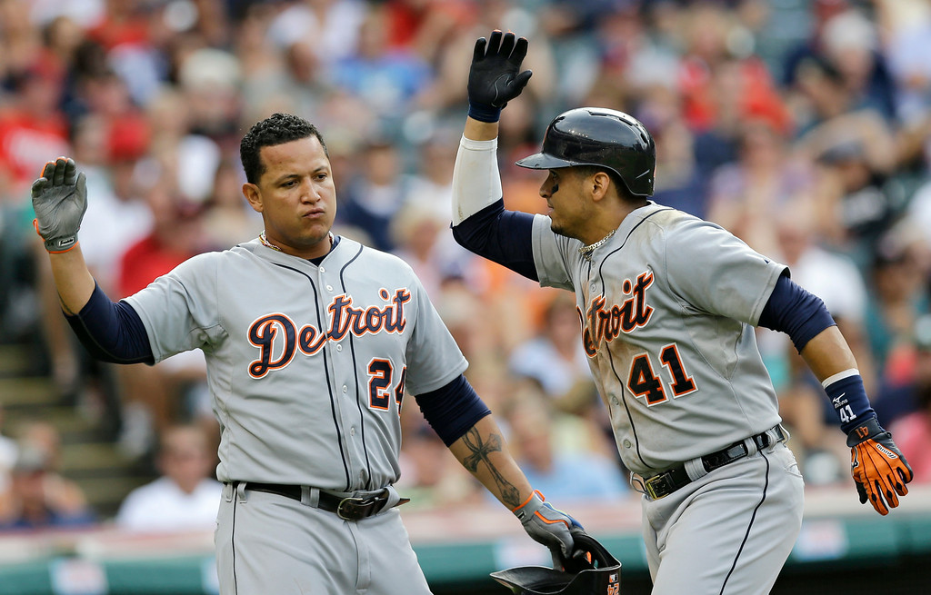 . Detroit Tigers\' Victor Martinez, right, and Miguel Cabrera celebrate after Martinez hit a two-run home run off Cleveland Indians starting pitcher Corey Kluber in the third inning of a baseball game, Monday, Sept. 1, 2014, in Cleveland. Cabrera scored on the play. (AP Photo/Tony Dejak)