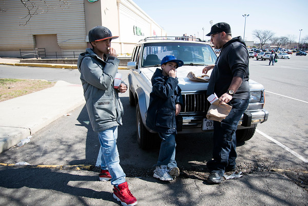 03/18/20 Wesley Bunnell | Staff Gabriel Ortiz, age 10 L, Christian Ortiz, age 8 middle, and step father Luis Morales dine on the hood of his car after getting takeout from Capital Lunch on Wednesday March 18, 2020. Restaurants were forced to stop inside dining and turn to take out and delivery only to help stop the speed of the Coronavirus.
