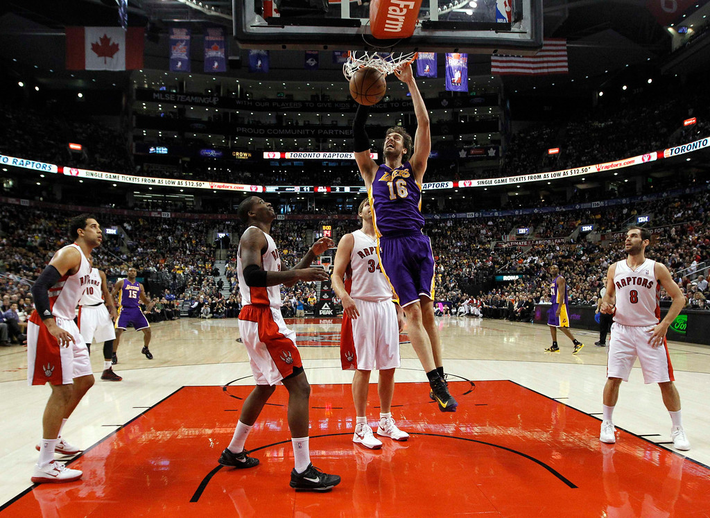 . Los Angeles Lakers\' Pau Gasol (C) goes up for a slam dunk past the Toronto Raptors during the first half of their NBA basketball game in Toronto, January 20, 2013.  REUTERS/Mark Blinch