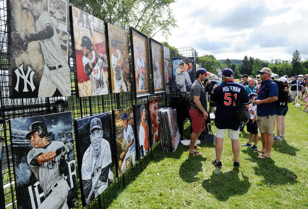 . Fans buy baseball merchandise before the start of an National Baseball Hall of Fame induction ceremony at the Clark Sports Center on Sunday, July 29, 2018, in Cooperstown, N.Y. (AP Photo/Hans Pennink)