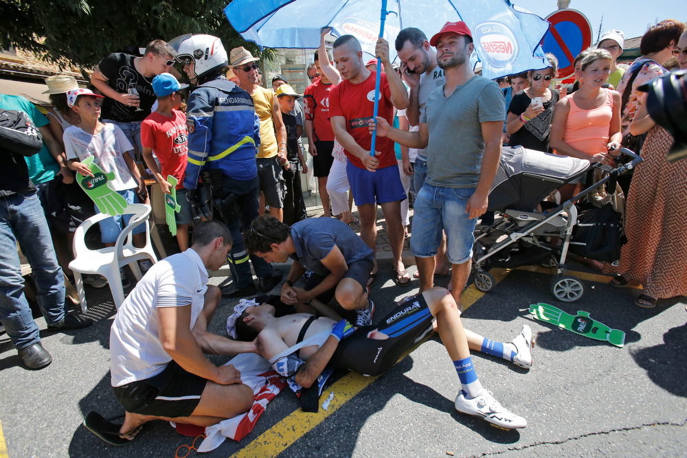 . Spectators shield Spain\'s David De La Cruz Melgarejo from the sun after he crashed when riding in the breakaway in Oingt, during the twelfth stage of the Tour de France cycling race over 185.5 kilometers (115.3 miles) with start in Bourg-en-Bresse and finish in Saint-Etienne, France, Thursday, July 17, 2014. De La cruz had to withdraw from the race because of his injuries. (AP Photo/Christophe Ena)