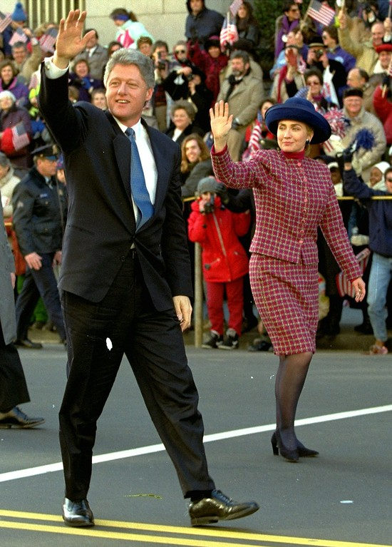. FILE - President Clinton and his wife Hillary Rodham Clinton wave to the crowd as they walk down 15th Street in Washington  January 20, 1993 during the presidential inaugural parade. The first lady  picked a wool suit and matching wool coat designed by Oscar de la Renta to wear to her husband\'s 1997 inauguration but has not yet settled on a hat - a controversial item of her 1993 inaugural wardrobe. Four years ago, fashion critics panned the big, blue, brimmed velour number equipped with a hat pin that Mrs. Clinton wore to the ceremony. (AP Photo)