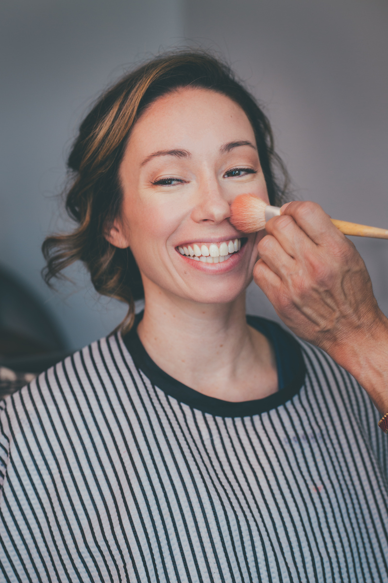 bride wearing pinstripe smock getting her makeup done before her wedding