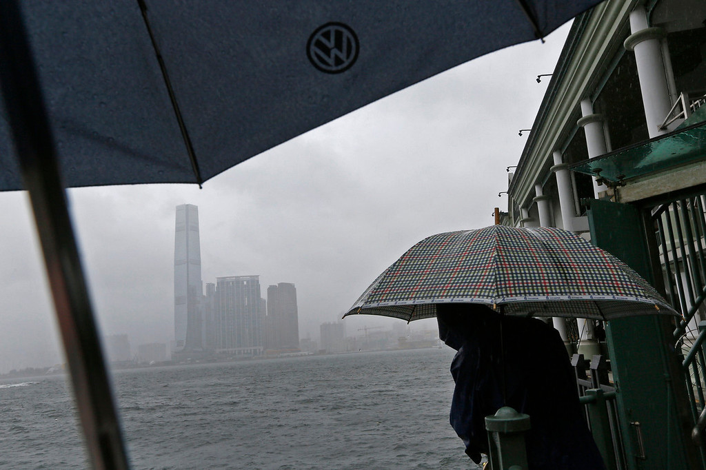 . A man throws a line for catches under strong wind at Hong Kong\'s Victoria Habour Tuesday, Aug. 13, 2013. The Observatory said Typhoon Utor intensified slightly as it moves towards the western coast of Guangdong. typhoon Utor h battered the northern Philippines on Monday, toppling power lines and dumping heavy rain across cities and food-growing plains. (AP Photo/Vincent Yu)