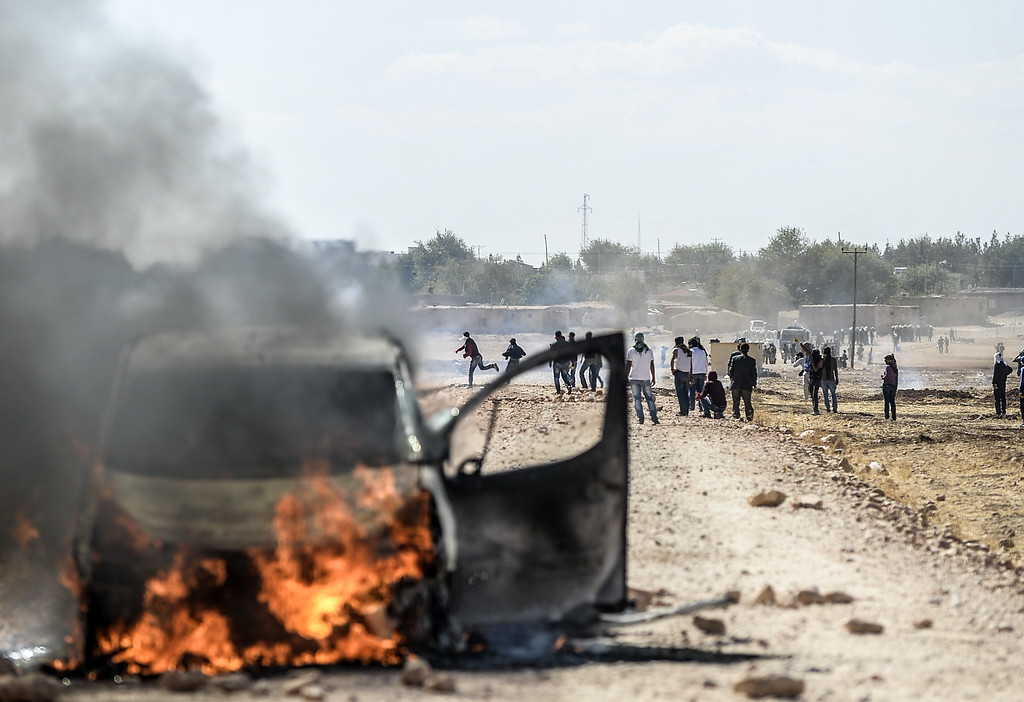 . Kurdish protestors clash with Turkish soldiers near the Syrian border after Turkish authorities temporarily closed the border at the southeastern town of Suruc in Sanliurfa province, on September 22, 2014. BULENT KILIC/AFP/Getty Images