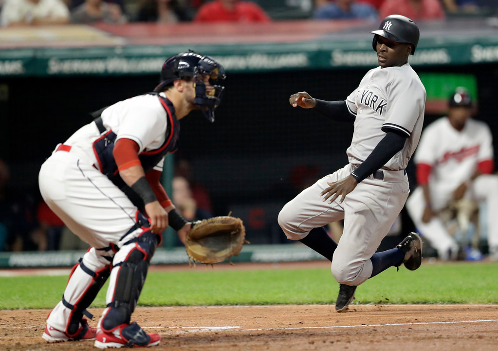 . New York Yankees\' Didi Gregorius scores as Cleveland Indians\' Yan Gomes waits for the ball during the eighth inning of a baseball game Thursday, July 12, 2018, in Cleveland. (AP Photo/Tony Dejak)