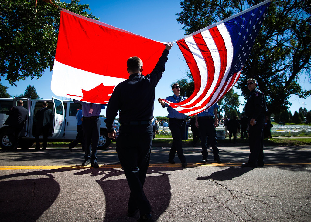 . Colorado Springs Fire Department Explorers and Firefighters prepare to display the Canadian and American flags before the start of the annual IAFF Fallen Fire Fighter Memorial at Memorial Park in Colorado Springs, Colo., on Saturday, Sept. 21, 2013.(AP Photo/The Gazette, Kent Nishimura)