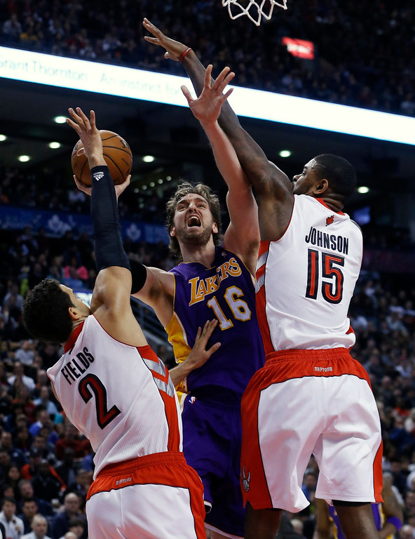 . Los Angeles Lakers\' Pau Gasol (C) goes to the basket against Toronto Raptors\' Landry Fields (L) and Amir Johnson (R) during the second half of their NBA basketball game in Toronto, January 20, 2013.     REUTERS/Mark Blinch