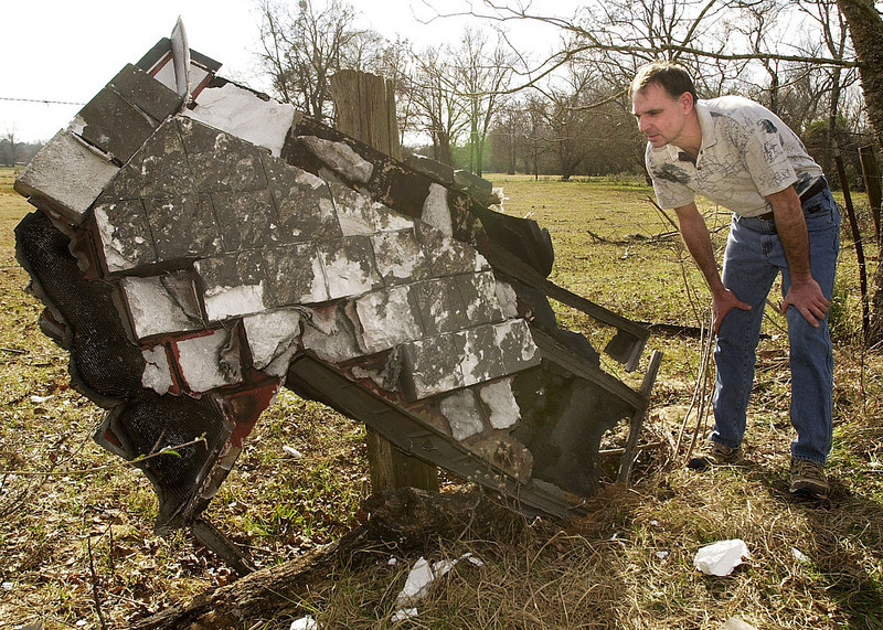 . Mac Powell examines a piece of debris, believed to be from the space shuttle Columbia, he found behind his home near Nacogdoches, Texas, Sunday, Feb. 2, 2003. (AP Photo/The Daily Sentinel, Andrew D. Brosig)