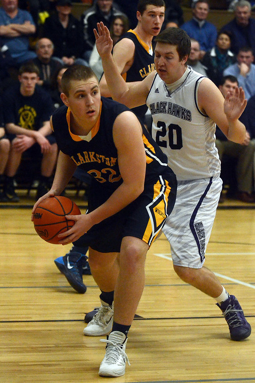 . Clarkston\'s #32 Jonah Newblatt looks to pass while guarded by Bloomfield Hills #20 Logan McDonald during their game at Bloomfield Hills High School, Tuesday January 28, 2014. Bloomfield Hills went on to win the game 74-62. (Vaughn Gurganian-The Oakland Press)
