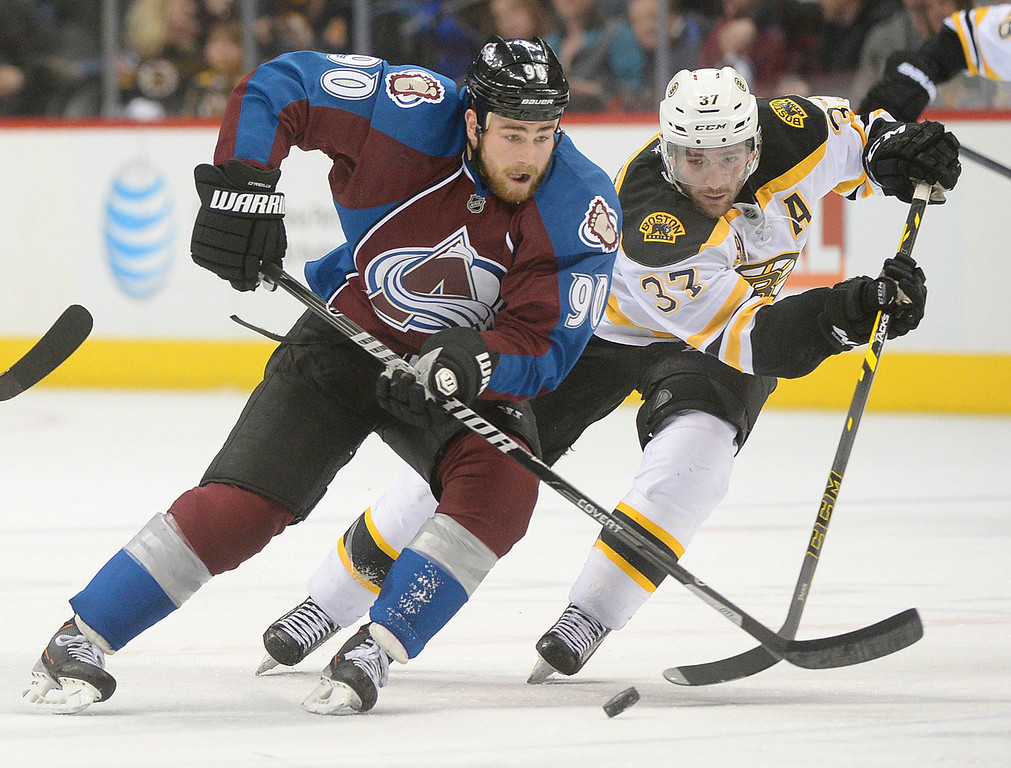 . Colorado center Ryan O\'Reilly (90) and Boston center Patrice Bergeron (37) raced for the puck in the third period. The Boston Bruins blanked the Colorado Avalanche 2-0 at the Pepsi Center Friday night, March 21, 2014. (Photo by Karl Gehring/The Denver Post)