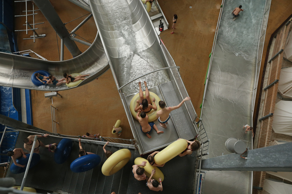 Description of . Visitors ride innertubes down a waterslide at the Tropical Islands indoor resort on February 15, 2013 in Krausnick, Germany. Located on the site of a former Soviet military air base, the resort occupies a hangar built originally to house airships designed to haul long-distance cargo. Tropical Islands opened to the public in 2004 and offers visitors a tropical getaway complete with exotic flora and fauna, a beach, lagoon, restaurants, water slide, evening shows, sauna, adventure park and overnights stays ranging from rudimentary to luxury. The hangar, which is 360 metres long, 210 metres wide and 107 metres high, is tall enough to enclose the Statue of Liberty.  (Photo by Sean Gallup/Getty Images)