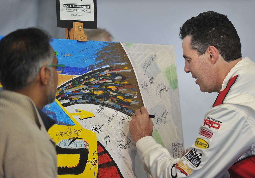 . 4/9/13 - Adam Carolla autographs a painting for auction, during media day for the 39th Annual Toyota Grand Prix of Long Beach. The celebrity/pro races spent the day practicing on the track, joking with their racing partners and giving interviews. Photo by Brittany Murray / Staff Photographer