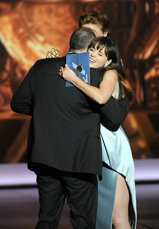 . Zooey Deschanel embraces Tony Hale, left, after he received the award for outstanding supporting actor in a comedy series to Tony Hale on stage at the 65th Primetime Emmy Awards at Nokia Theatre on Sunday Sept. 22, 2013, in Los Angeles.  (Photo by Chris Pizzello/Invision/AP)