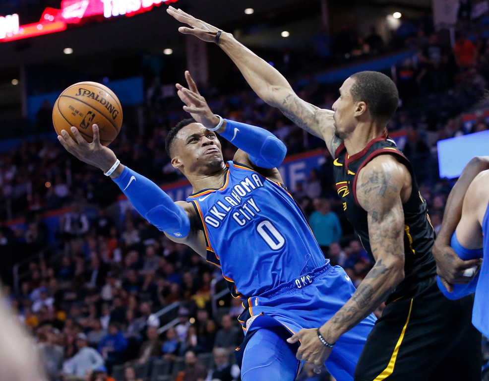 . Oklahoma City Thunder guard Russell Westbrook (0) shoots as Cleveland Cavaliers guard George Hill, right, defends, in the second half of an NBA basketball game in Oklahoma City, Tuesday, Feb. 13, 2018. (AP Photo/Sue Ogrocki)