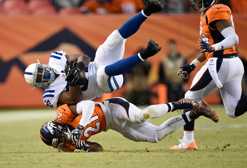 . Aqib Talib (21) of the Denver Broncos makes a tackle on Zurlon Tipton (37) of the Indianapolis Colts in the third quarter. The Denver Broncos played the Indianapolis Colts in an AFC divisional playoff game at Sports Authority Field at Mile High in Denver on January 11, 2015. (Photo by Joe Amon/The Denver Post)