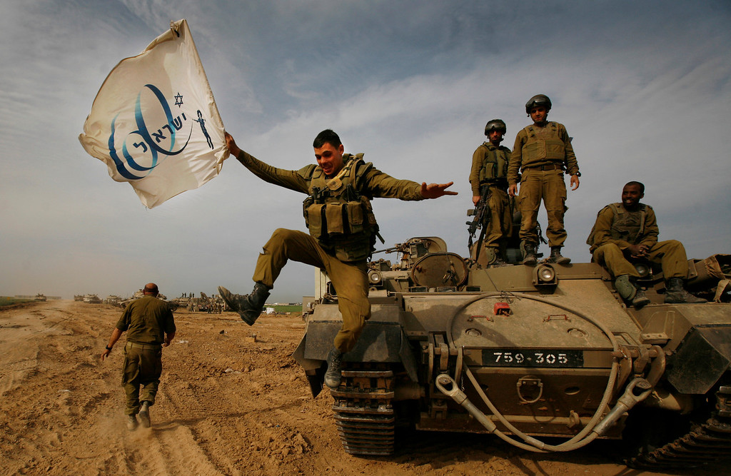 . FILE - In this Friday, Jan. 16, 2009 file photo made by Associated Press photographer Anja Niedringhaus, an Israeli soldier jumps off an armored vehicle carrying a flag of Israel\'s 60th anniversary as he celebrates with his unit their return from the Gaza Strip on the Israeli side of the border. (AP Photo/Anja Niedringhaus, File)