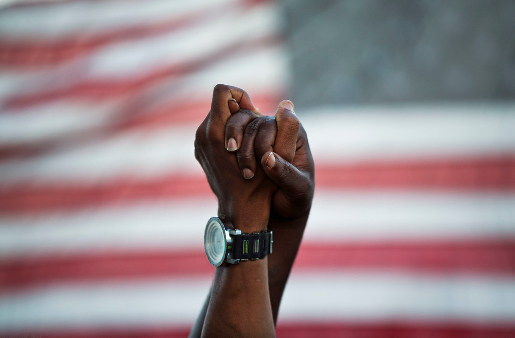 . People join hands against the backdrop of an American flag as thousands of marchers meet in the middle of Charleston\'s main bridge in a show of unity after nine black church parishioners were gunned down during a Bible study, Sunday, June 21, 2015, in Charleston, S.C. (AP Photo/David Goldman)