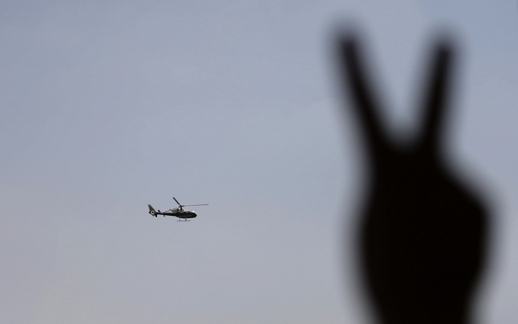 . A police helicopter flies over the presidential palace, as a man flashes the victory sign, in Cairo, Egypt, Tuesday, July 2, 2013. (Associated Press: Hassan Ammar)