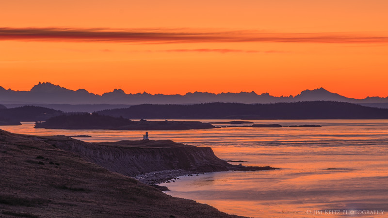 Wide-angle view of Cattle Point lighthouse & peninsula before sunrise - on San Juan Island. The Cascade Mountain range is the jagged line along the horizon, back on the mainland.