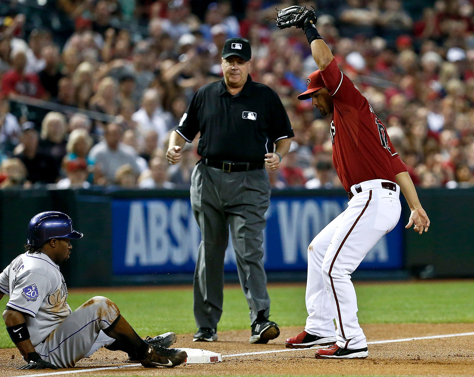 . Colorado Rockies\' Eric Young Jr., left, is tagged out  third base by Arizona Diamondbacks\' Eric Chavez, right, as umpire Gary Cederstorm looks on during the first inning of a baseball game, on Sunday, April 28, 2013, in Phoenix. (AP Photo/Ross D. Franklin)