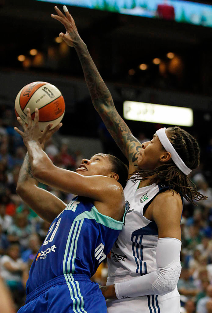 . New York Liberty guard Alex Montgomery tries to put the ball in the basket against Minnesota Lynx guard Seimone Augustus in the first half. (AP Photo/Stacy Bengs)