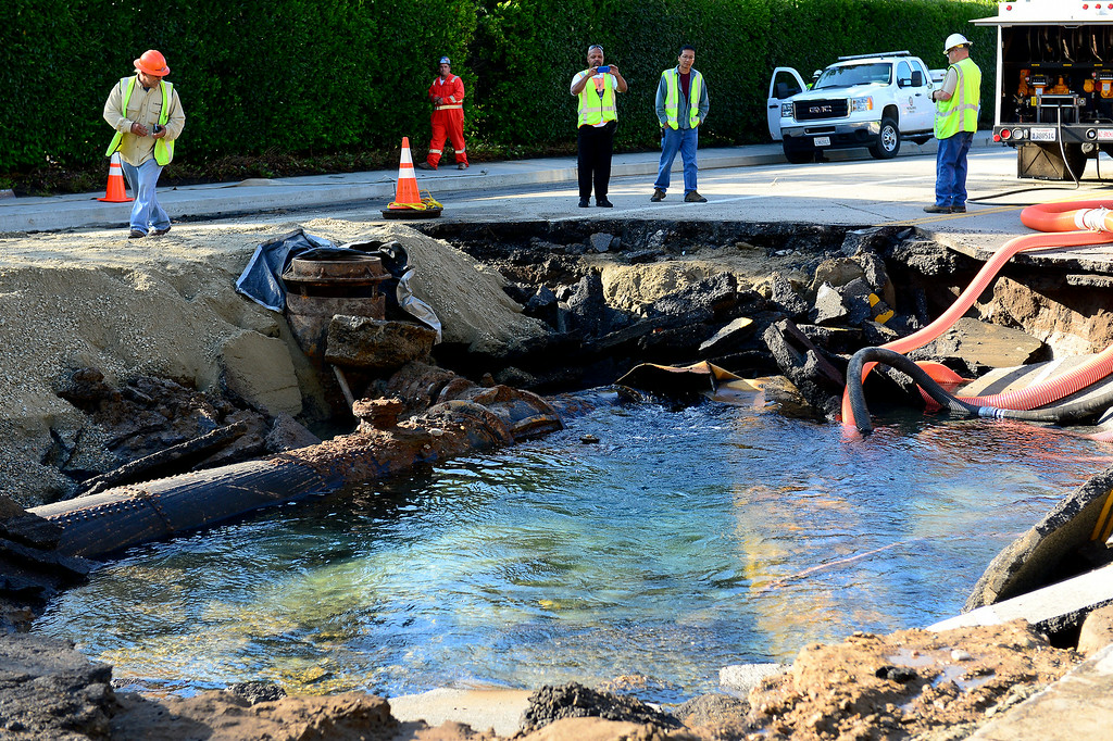 . The water eruption came from the busted connection of 1921 pipe, left, and a 1956 pipe, right, on Sunset Boulevard near UCLA, Wednesday, July 30, 2014. (Photo by Michael Owen Baker/Los Angeles Daily News)