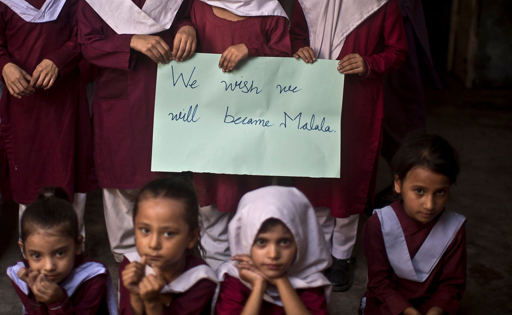 . Pakistani school children hold a hand-written sign during a special class to commemorate the anniversary of Malala Yousufzai\'s shooting by Taliban, at a school in Rawalpindi, Pakistan, Wednesday, Oct. 9, 2013. One year after a Taliban bullet tried to silence Malala\'s demand for education, she has published a book and is a contender for the Nobel Peace Prize. But the militants threaten to kill her should she dare return home from Britain to Pakistan, and the principal at her old school says that as Malala\'s fame has grown, so has fear in her classrooms. (AP Photo/Muhammed Muheisen)